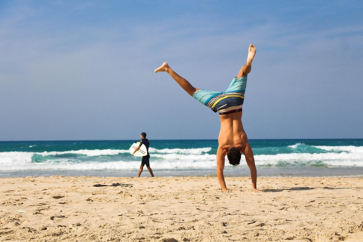 a man is standing upside down on his hands on the beach