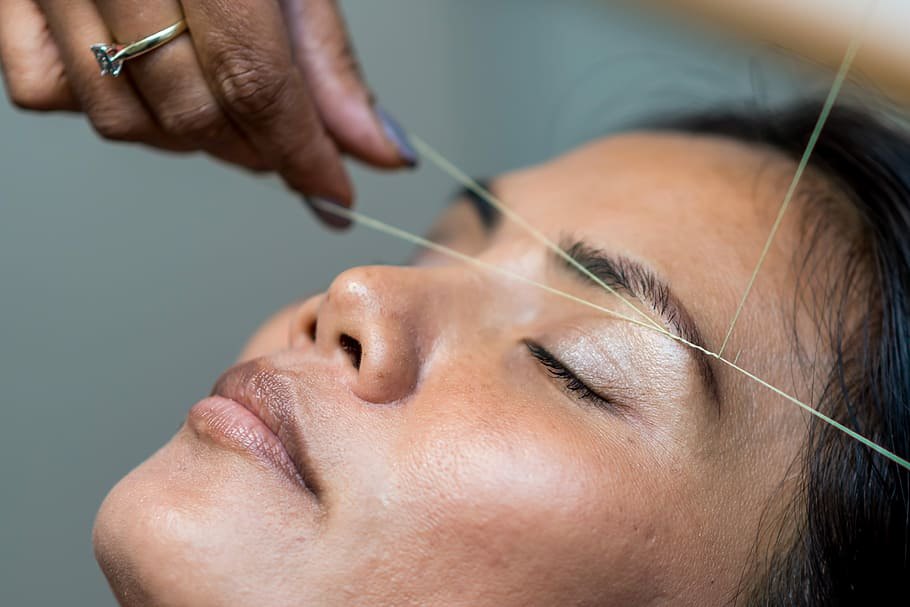 a woman removes her eyebrows hair by threading method