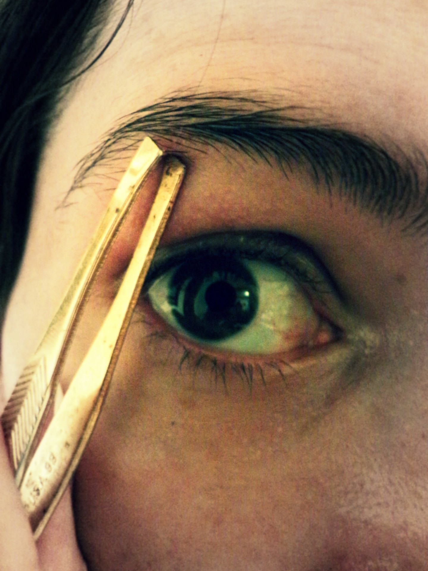a woman uses a tweezer to remove unwanted hair from eyebrows