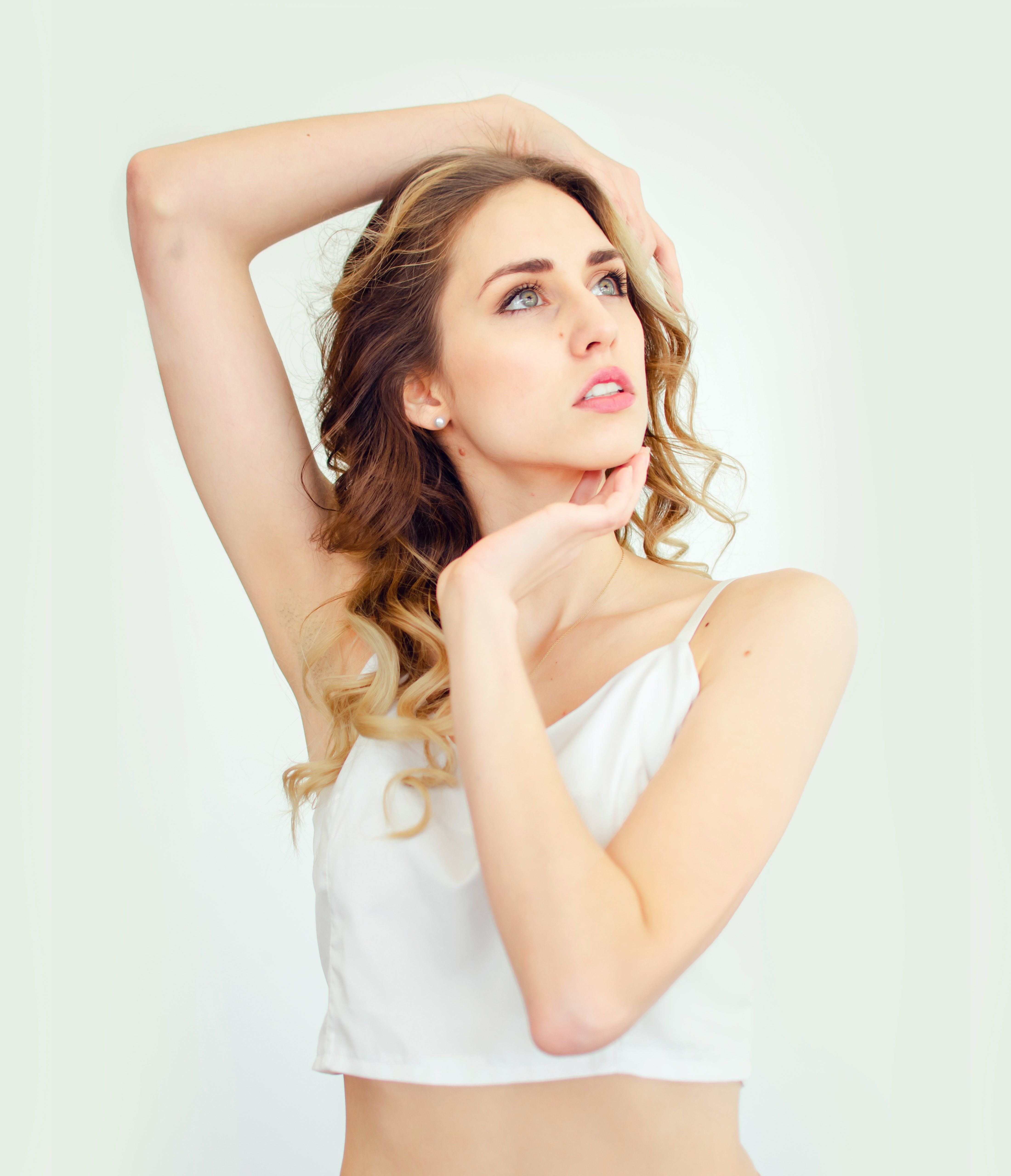 a woman raising her arm with smooth underarm area after using depilatory cream