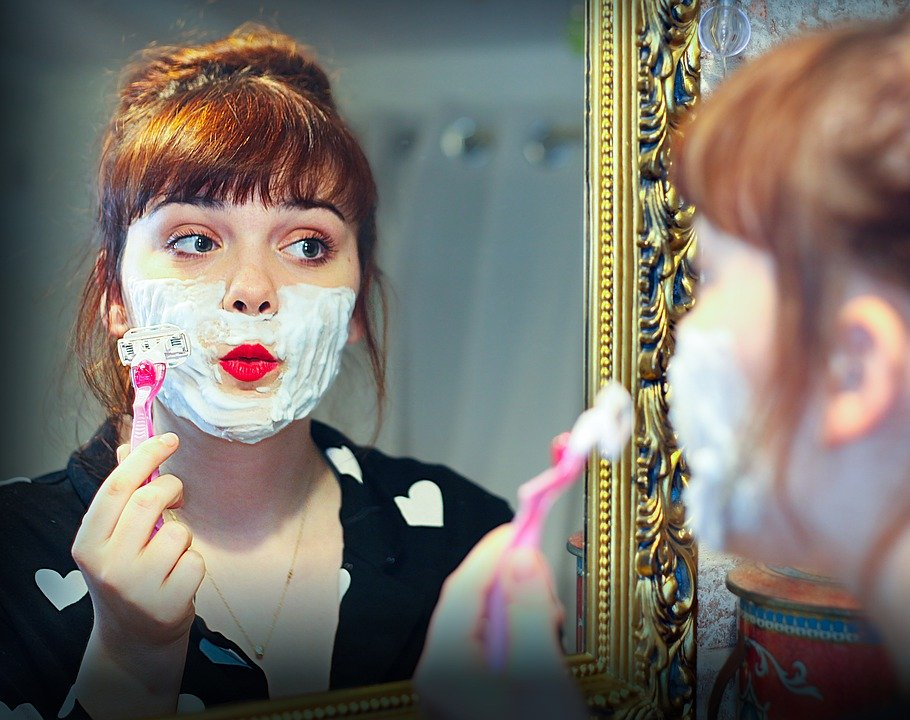 a woman shaving her face with a razor