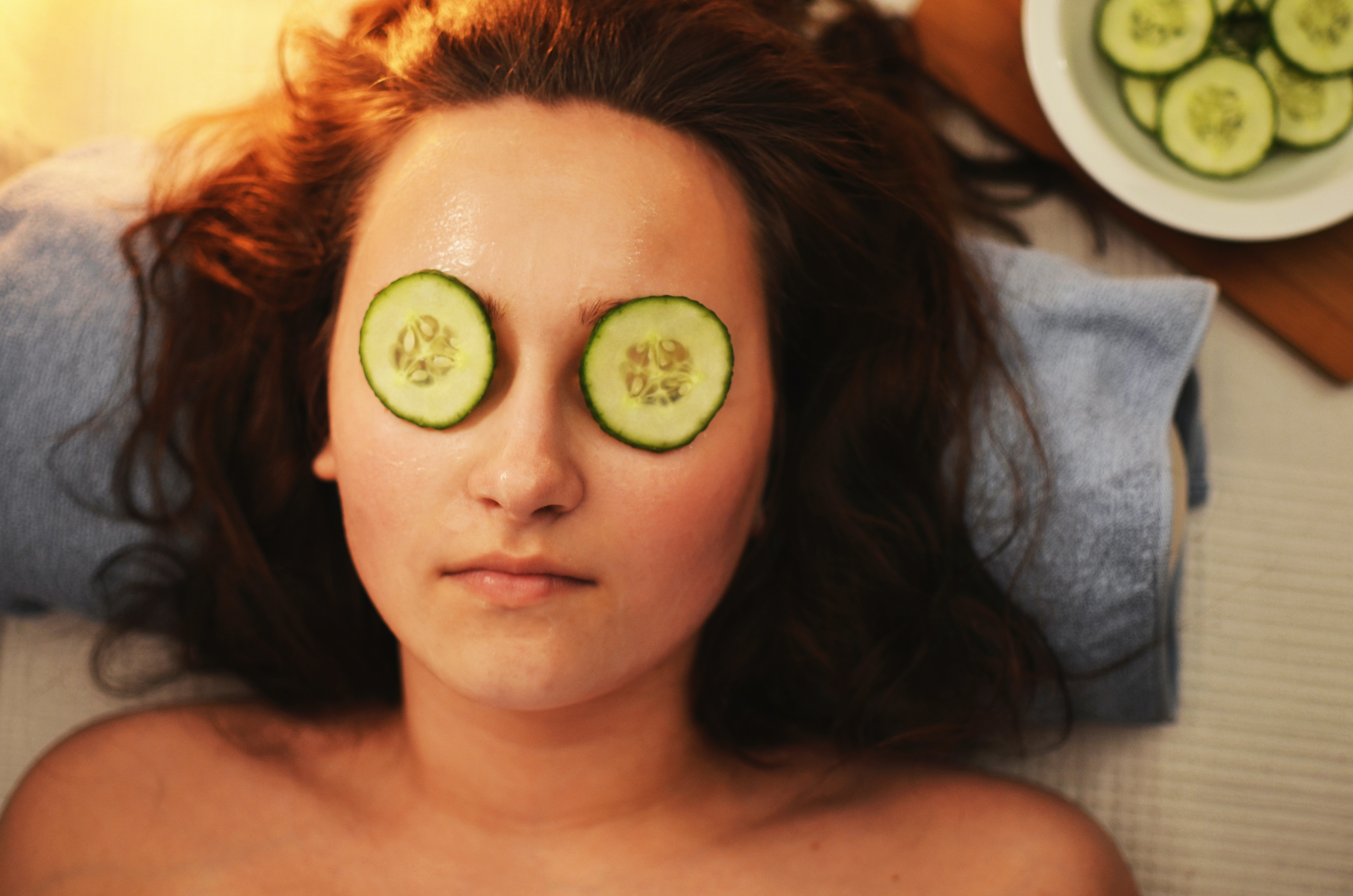 a cucumber slices on the eye of a woman