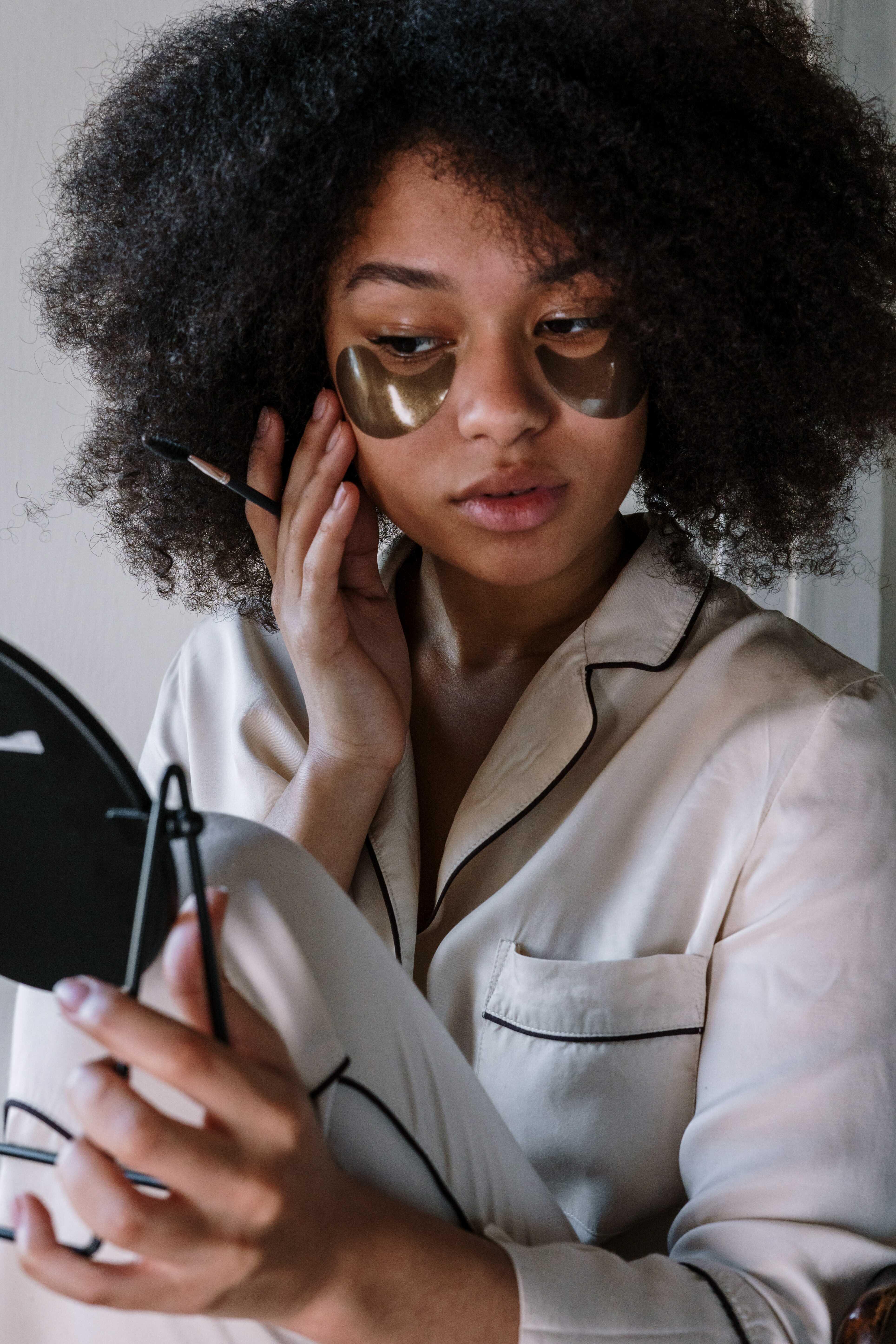 a dark tone woman putting eye patch under her eyes