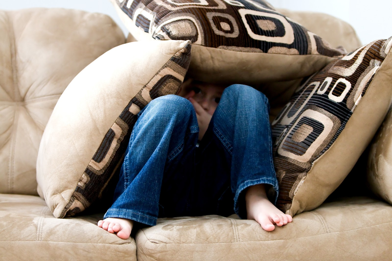 a child is covering himself with cushions