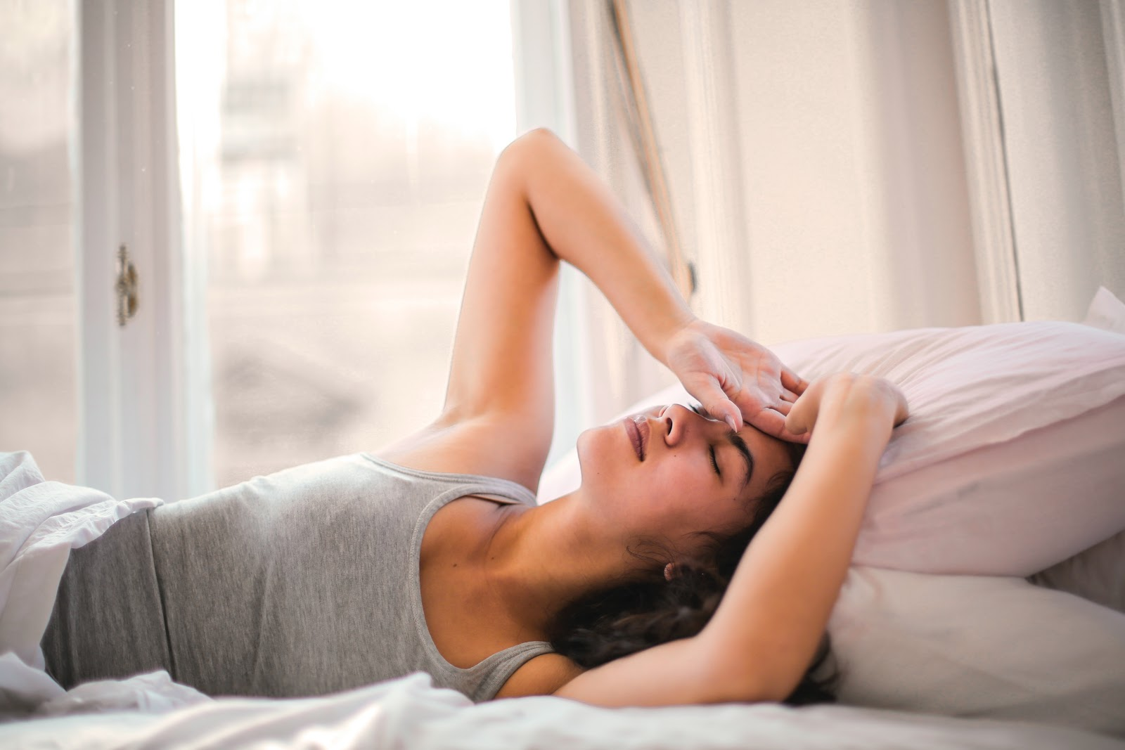 a woman is lying on the bed after waking up