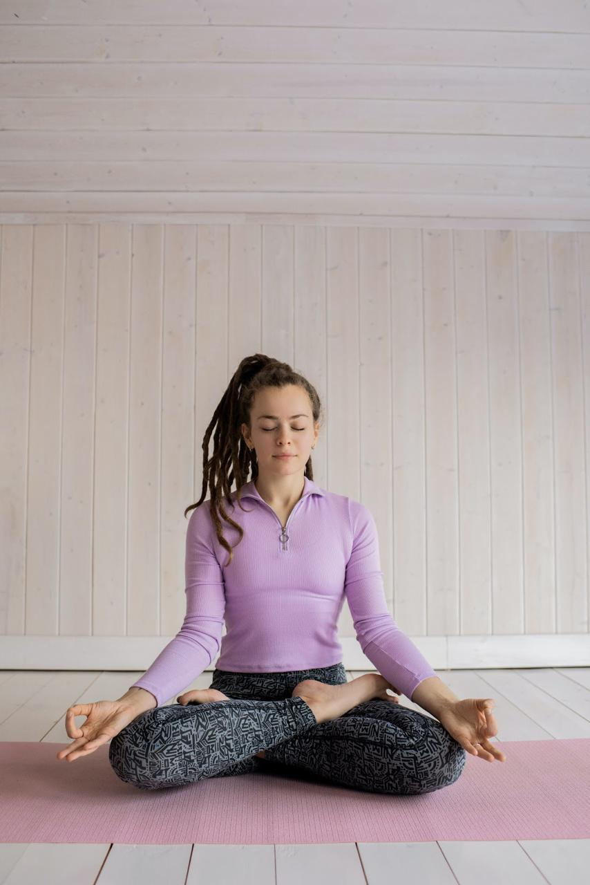 a young woman is practicing meditation