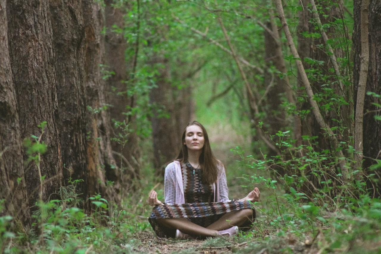 a woman is sitting in the jungle doing meditation