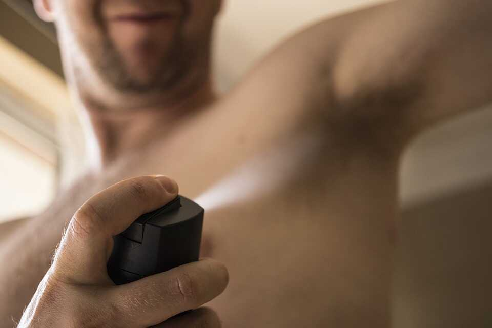 a man using deodorant spray on his underarm