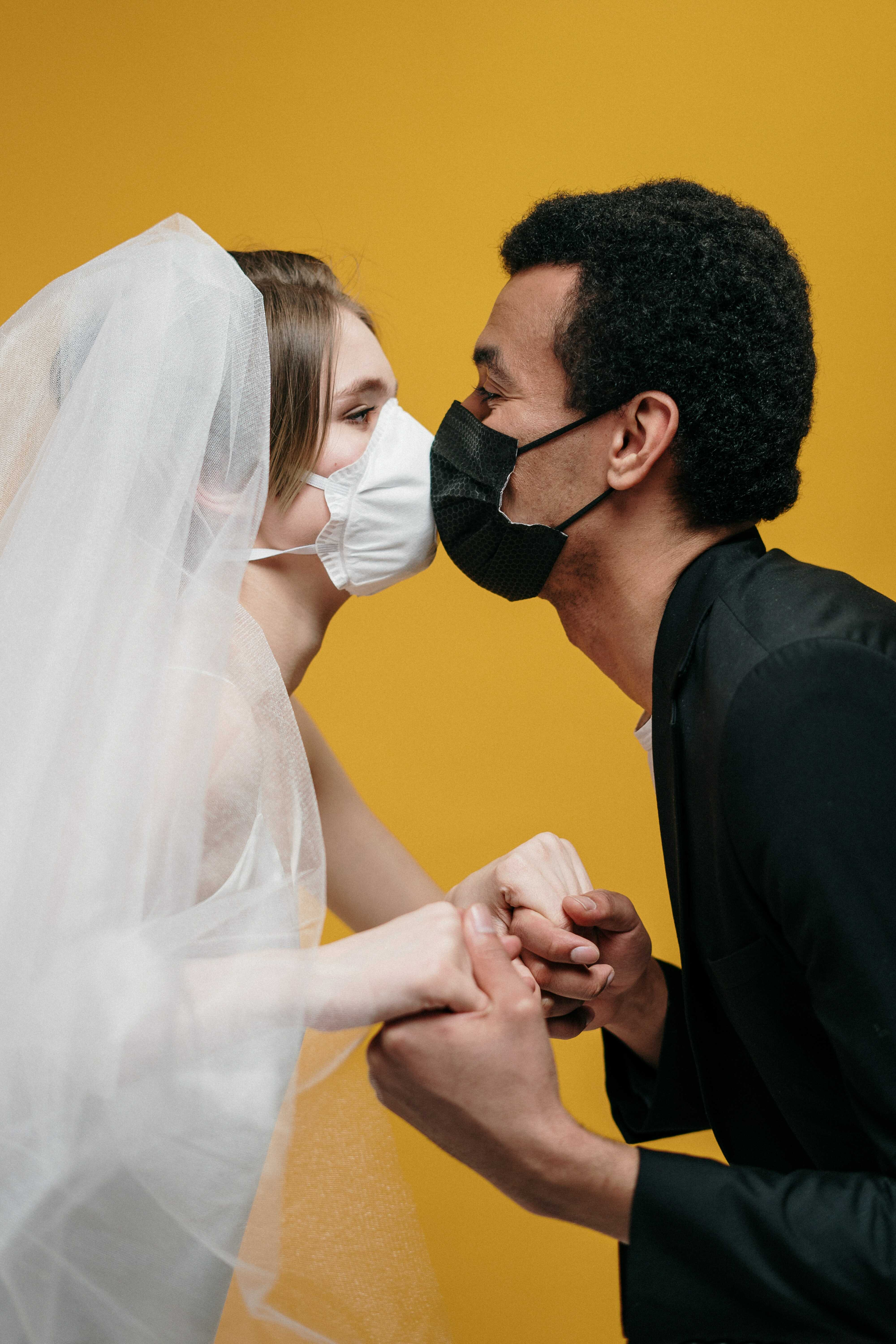a bride and a groom with a mask