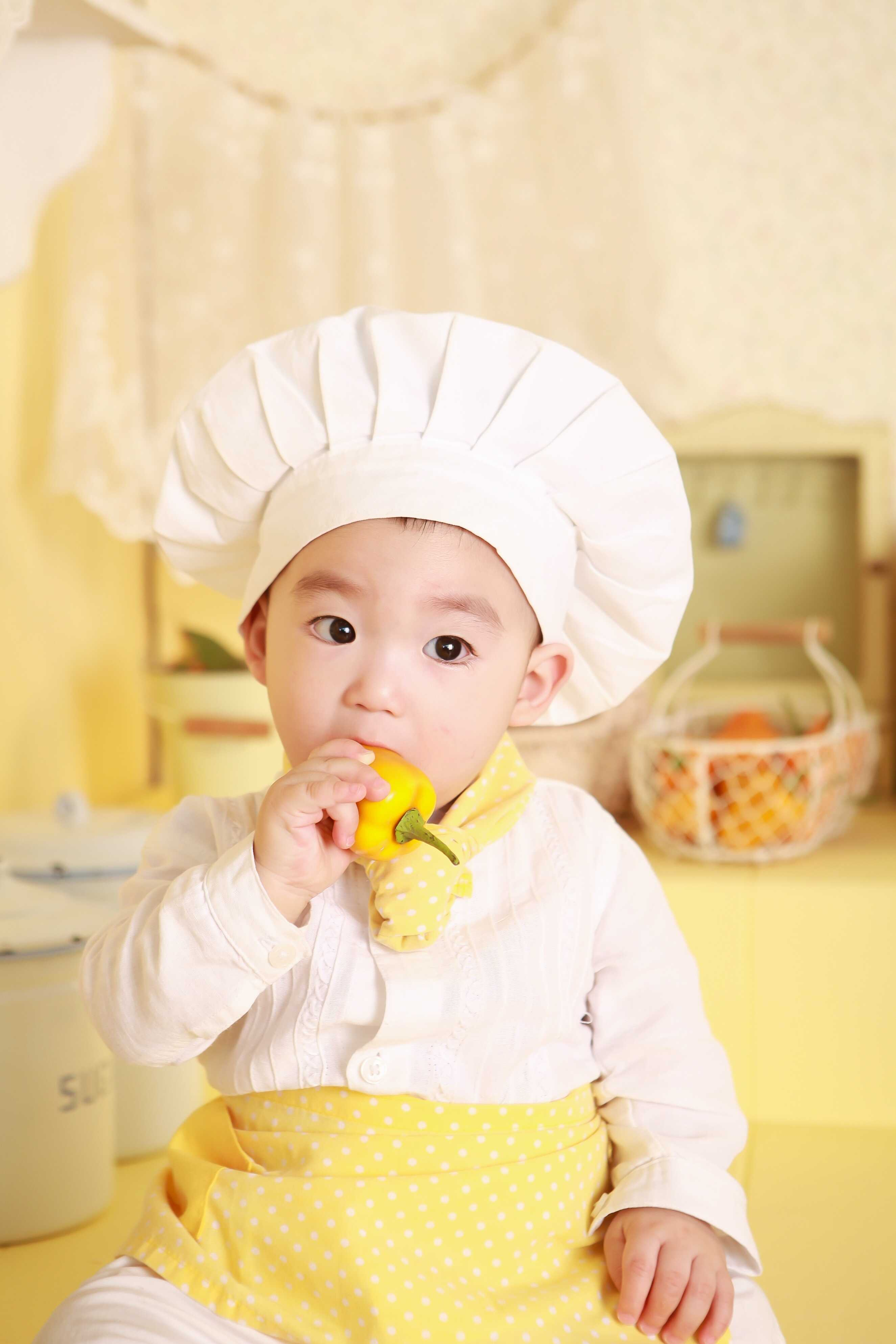 a baby with white outfit like a chef