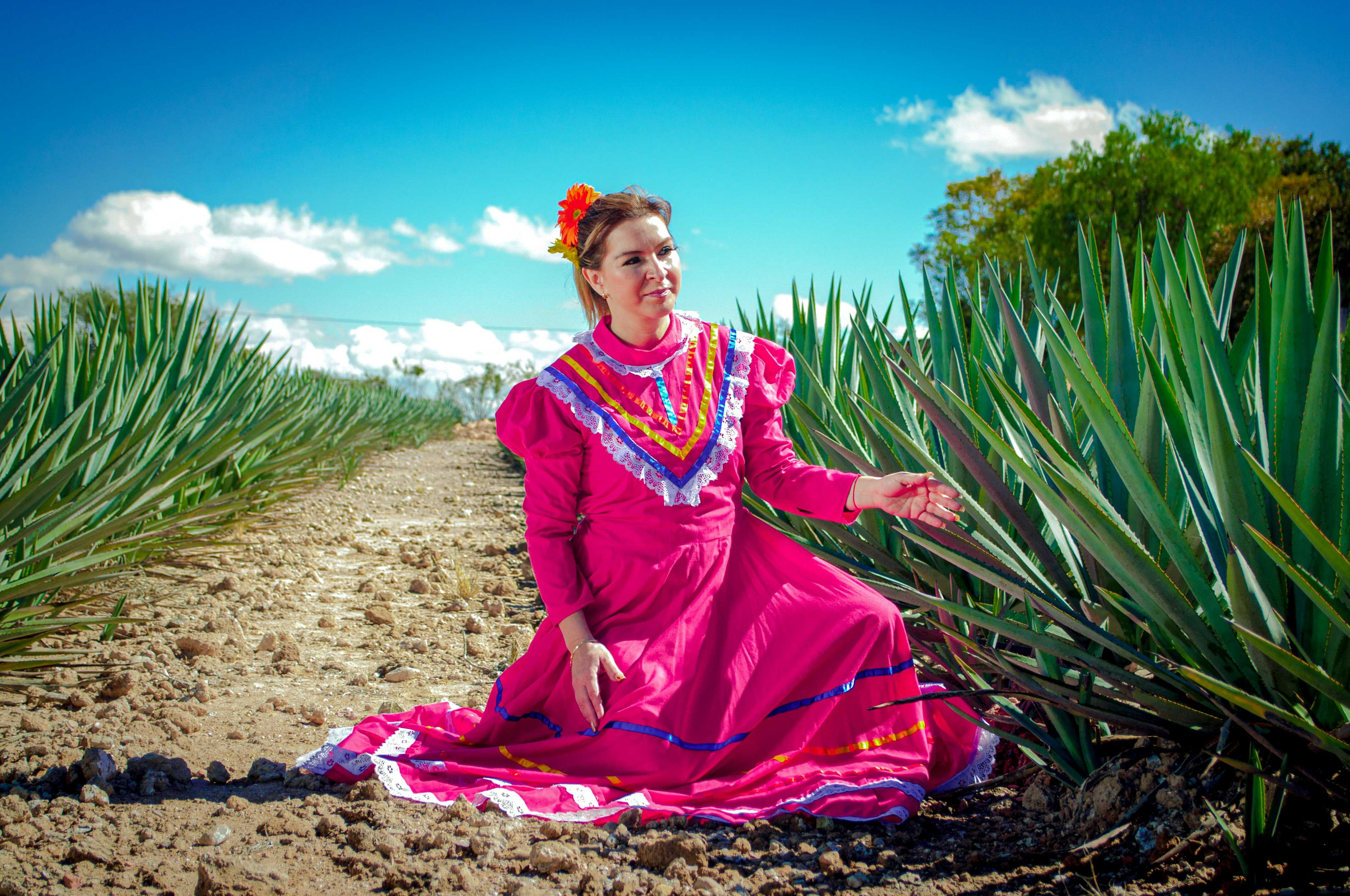 a farmer woman wears a pink color in among grasses
