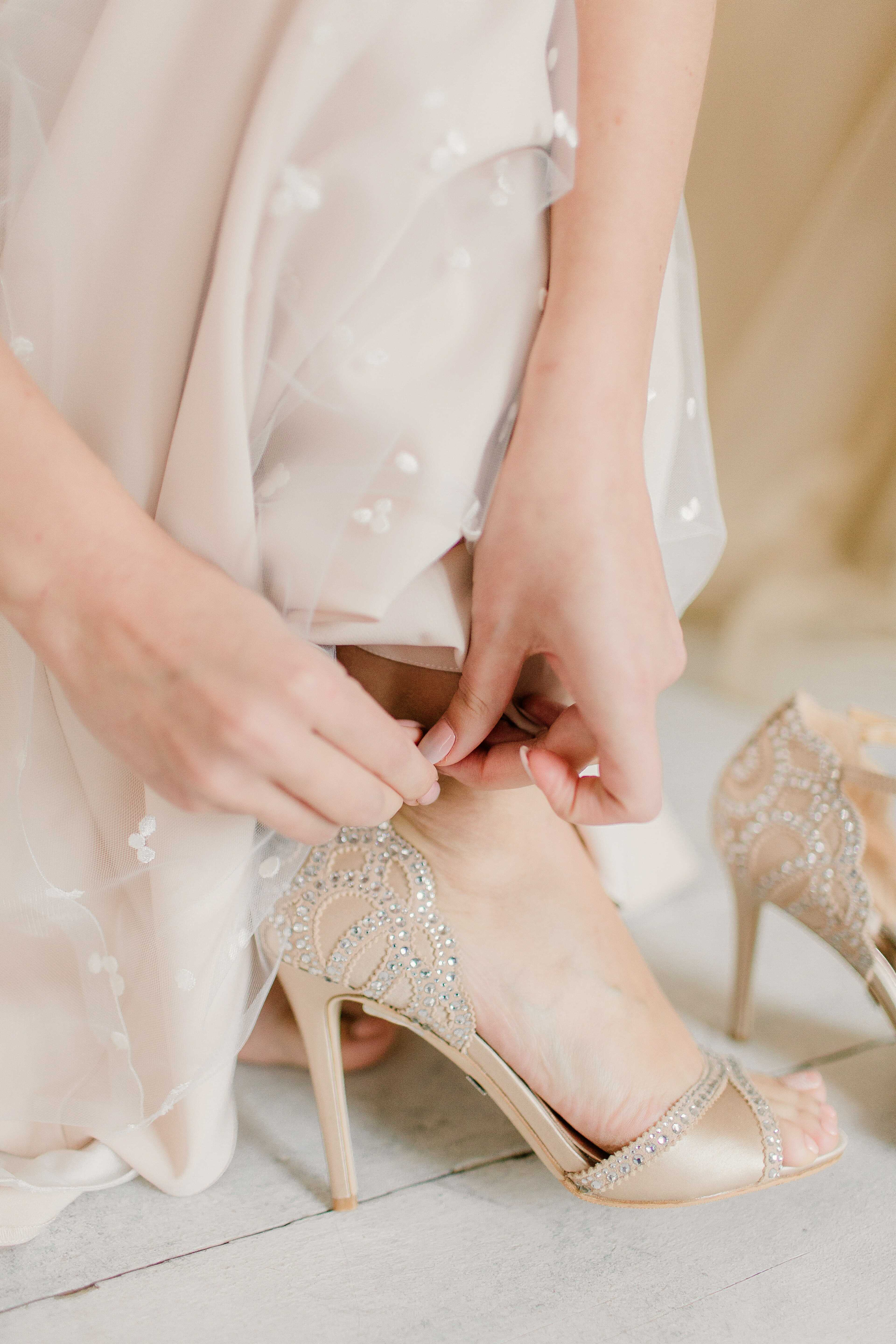 a woman is tightening her heel strap