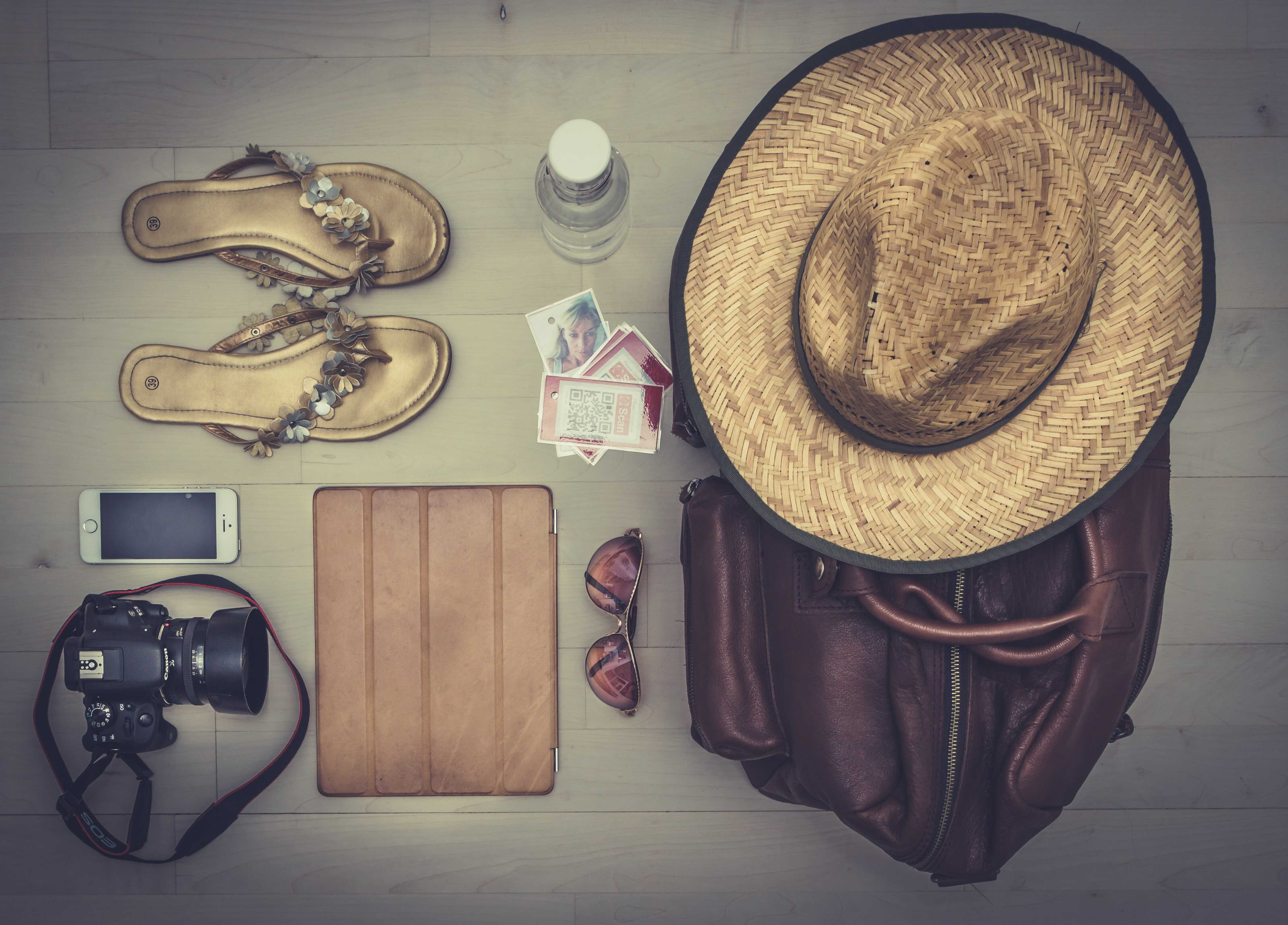 a photo of summer needs as a flip flop, camera, swimwear, and hat