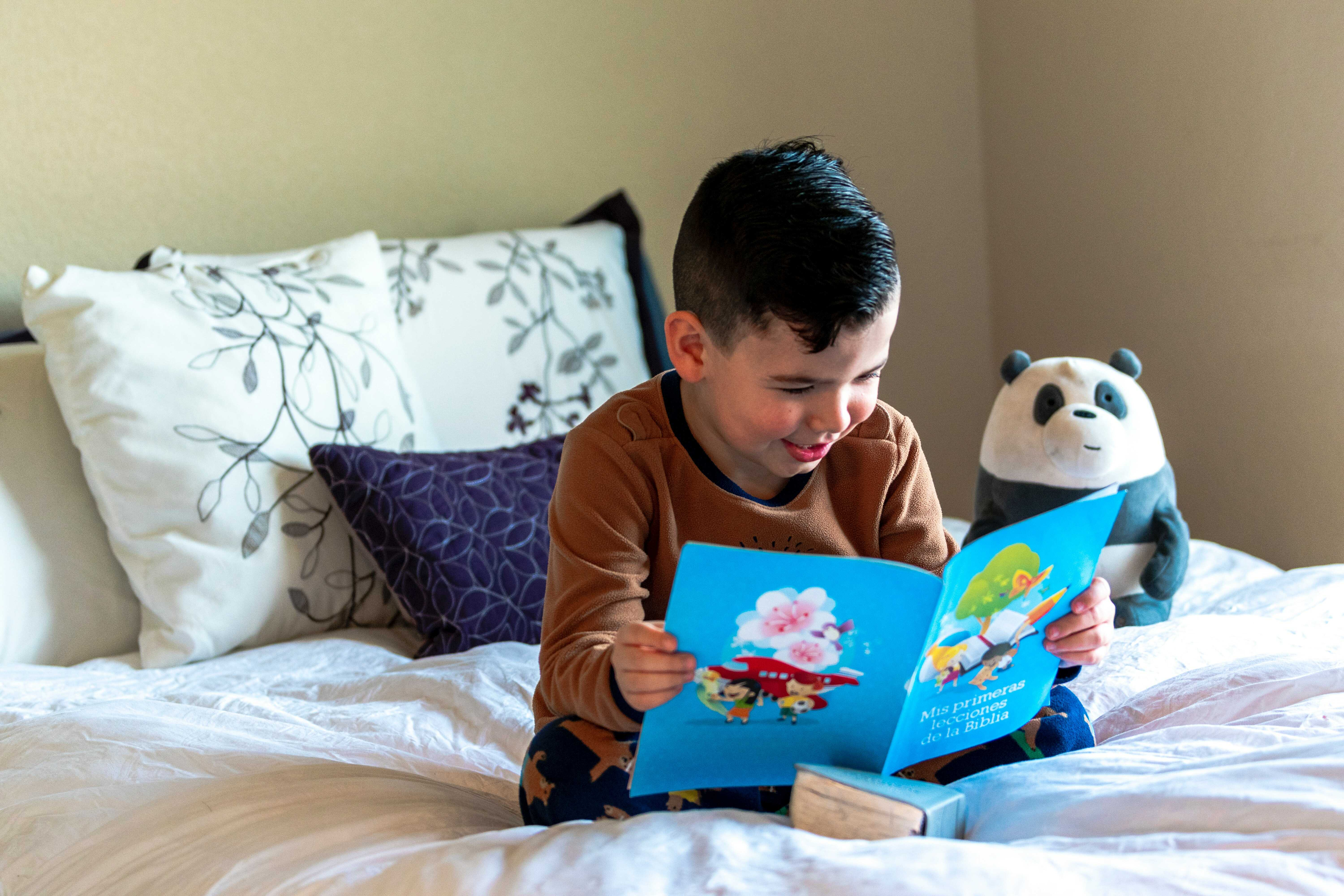 a boy reading a book on the bed