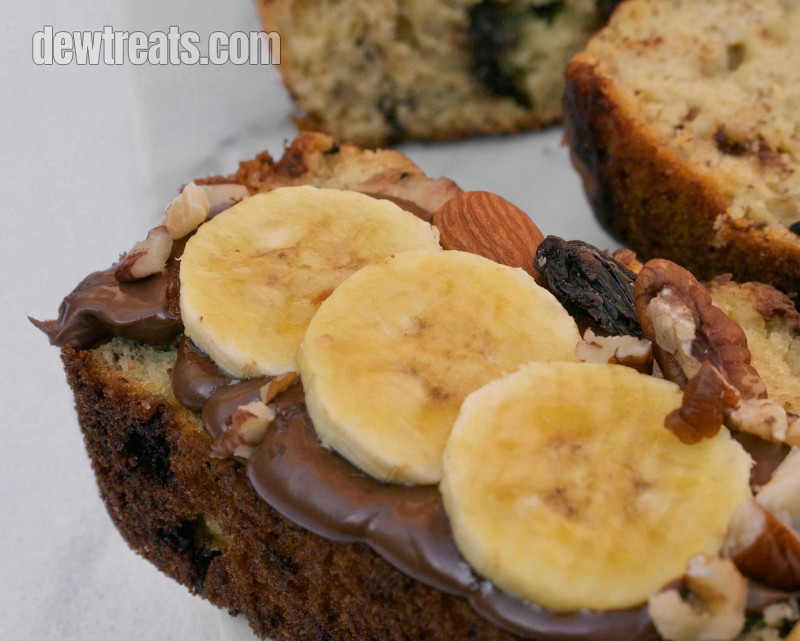 a slice of banana bread with chocolate cream, banana slices, and some nuts as a topping
