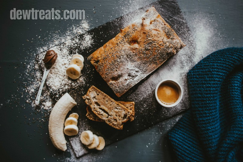 banana bread with banana and cup of coffee; a tsp of chocolate is added